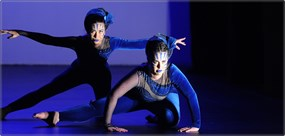 Two girls crouching and performing on a purple lit stage