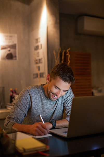 Young man looking down and  smiling while working at desk