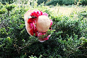 A staw hat with pink flowers hanging on a green hedge