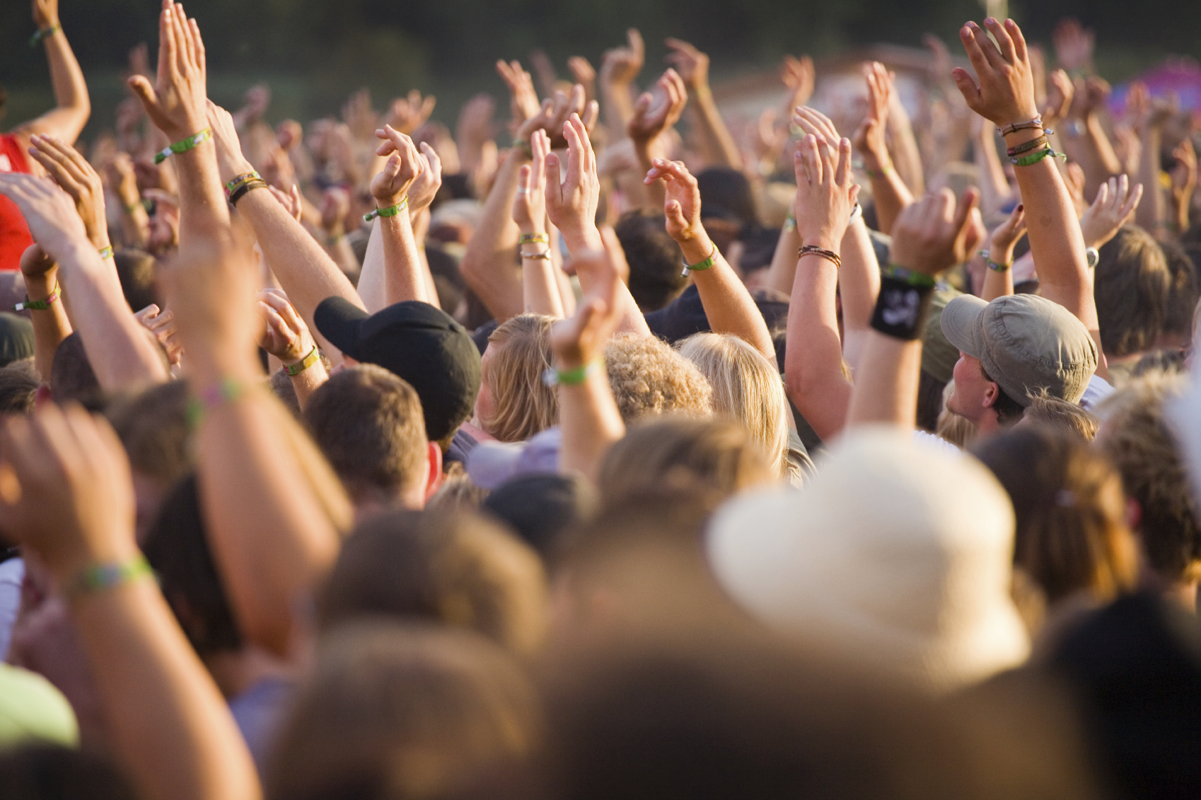 crowd at a festival event with their hands in the air