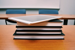A stack of school books and ipad on a wooden desk