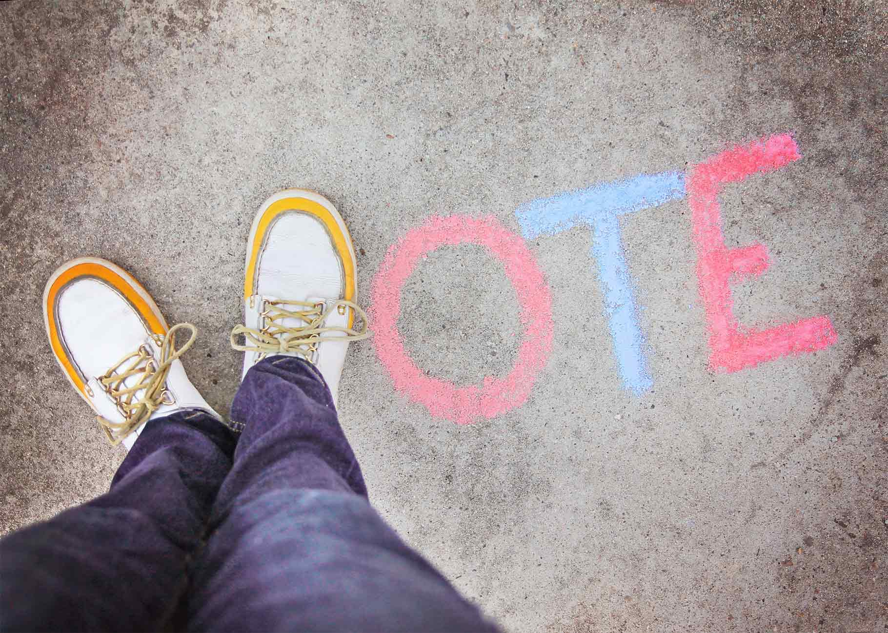 The word vote spelt by feet in the shape of a V and then chalk for OTE