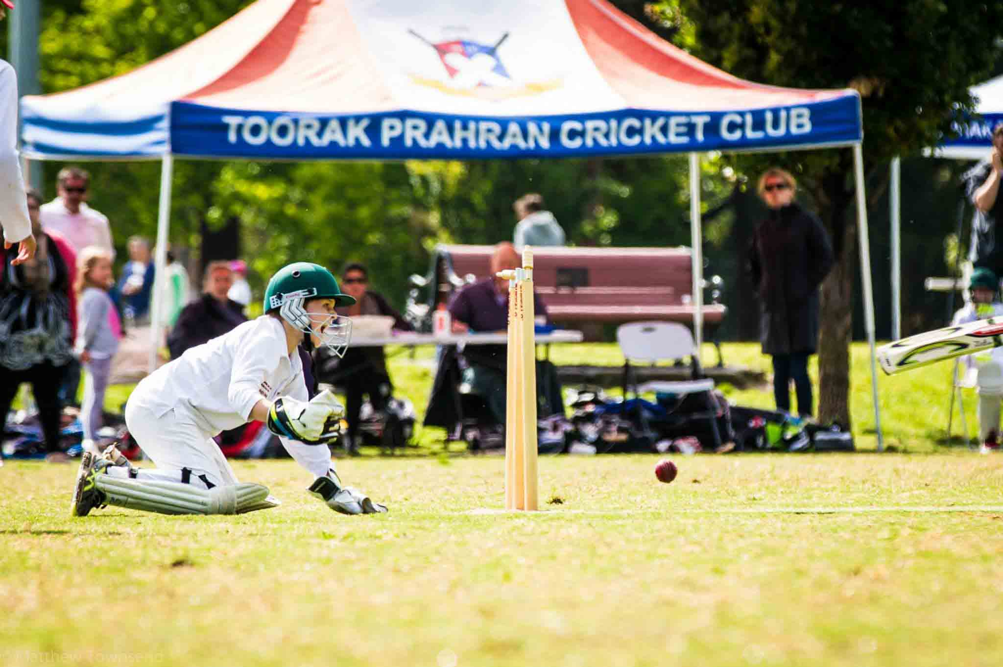 A boy kneeling on the ground playing cricket
